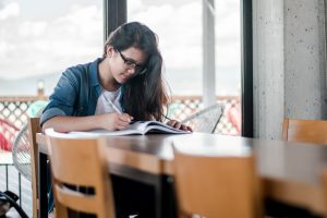 young woman reading a book with pen