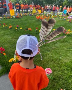 Community members gathering at a memorial for the 215 children whose remains were found at Kamloops Indian Residential School. A young child is in the foreground with an orange shirt on and four feathers placed at the back of his baseball cap.