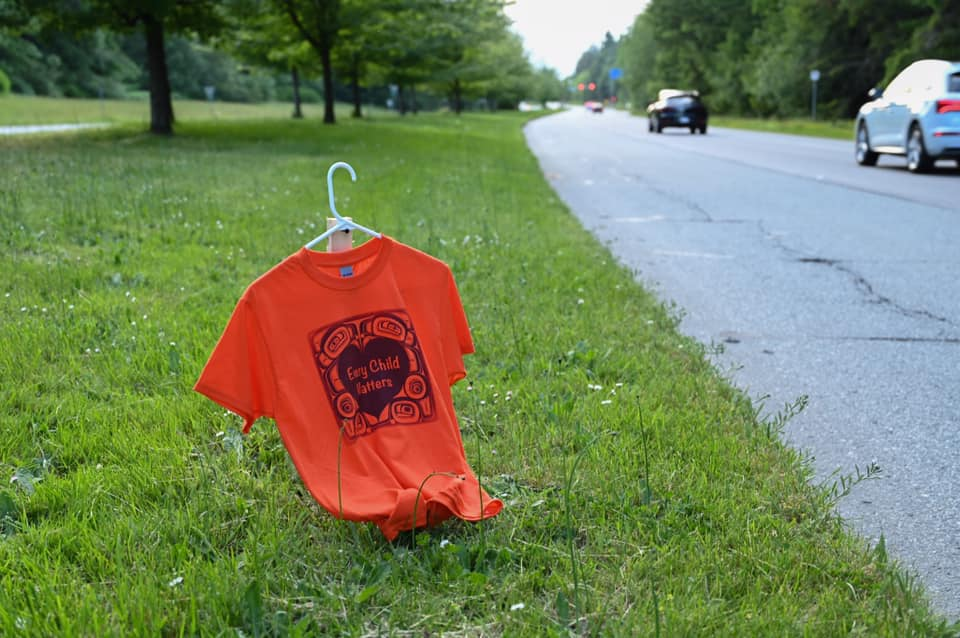 """An orange shirt that says """"Every Child Matters"""" hangs on a white clothes hanger which is held up by a wooden stake. It is placed on a grassy boulevard, with cars driving on the right hand side."""