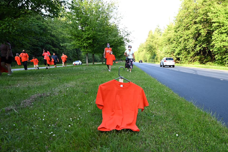 People walking on a grass boulevard between two rows. An orange shirt hangs in the foreground.