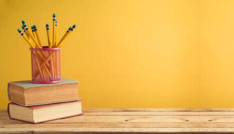 pencils on desk with books and a yellow wall behind